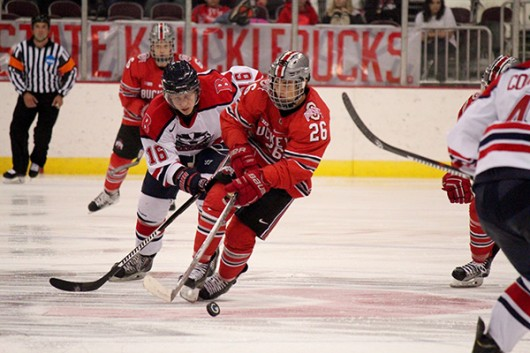 Freshman forward Mason Jobst (26) skates with the buck during an exhibition match against Brock University on Oct. 3 at the Schottenstein Center. OSU won, 4-0. Credit: Kaley Rentz / Asst. Sports Director