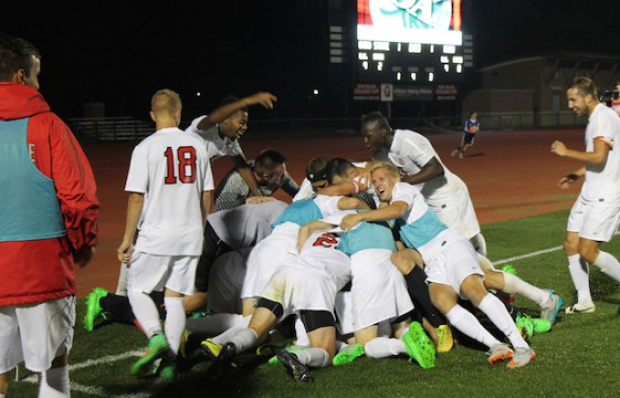 The Ohio State men's soccer team piles on top of midfielder Christian Soldat (13) after he scores the game winning goal with 3 seconds remaining in the second period of extra time during the men's soccer game against Bowling Green State University at Jesse Owens Memorial Stadium in Columbus, Ohio on October 7, 2015. OSU won 2-1. Eric Weitz / Lantern Photographer