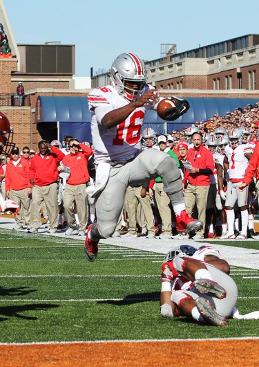 Redshirt sophomore quarterback J.T. Barrett (16) leaps into the end zone for a touchdown during OSU's 28-3 win over Illinois on Nov. 14 in Champaign, Illinois. Credit: Samantha Hollingshead | Photo Editor