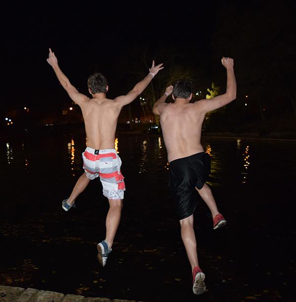 Two students jump into Mirror Lake on Nov. 25 during the Mirror Lake jump. Credit: Robert Scarpinito | Copy Chief