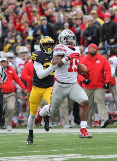 OSU junior running back Ezekiel Elliott (15) runs with the ball in a game against Michigan on Nov. 28 at Michigan Stadium. OSU won, 42-13. Credit: Samantha Hollingshead | Photo Editor