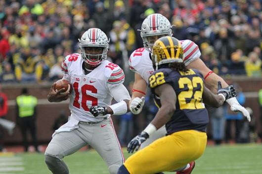 Ohio State redshirt sophomore quarterback J.T. Barrett (16) tries to get around Michigan senior safety Jarrod Wilson (22) during a game on Nov. 28 in Ann Arbor, Michigan. OSU won 42-13. Credit: Samantha Hollingshead | Photo Editor