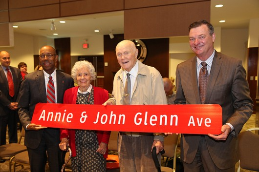 President Michael Drake, Annie Glenn, John Glenn, Board of Trustees Chair Jeffrey Wadsworth pose with the street sign for the newly named avenue on OSU campus. Credit: Courtesy of OSU