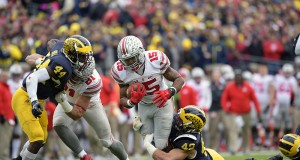 OSU junior running back Ezekiel Elliott (15) carries the ball while Michigan linebacker Ben Gedeon (42) attempts to tackle him during a game on Nov. 28. OSU won, 42-13. Credit: Samantha Hollingshead | Photo Editor