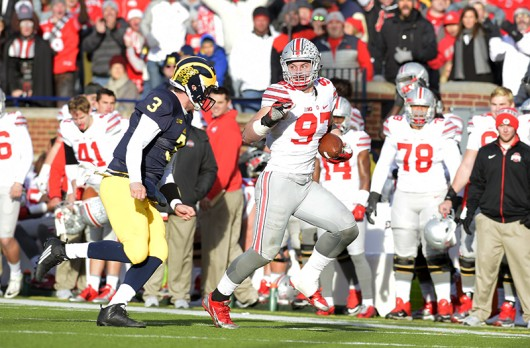OSU junior defensive end Joey Bosa (97) runs with the football after intercepting a pass in a game against Michigan on Nov. 28 at Michigan Stadium. OSU won, 42-13. Credit: Samantha Hollingshead | Photo Editor