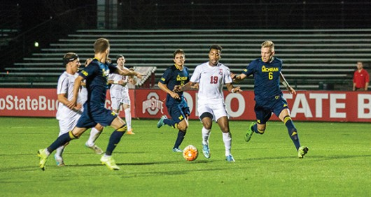 Ohio State then-sophomore Marcus McCrary (19) dribbles the ball through a group of Michigan players during a soccer game at Jesse Owens Memorial Stadium on Nov. 4, 2015. Credit: Lantern File Photo