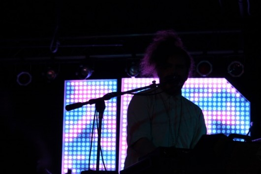 Daniel Zott silhouetted against the JR JR backdrop while playing keyboard. Credit: Mason Swires | Lantern reporter