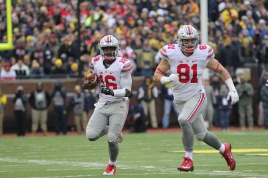 OSU redshirt sophomore J.T. Barrett (16) carries the ball while redshirt senior tight end Nick Vannett (81) looks for a defender to block during a game against Michigan on Nov. 28. OSU won, 42-13. Credit: Samantha Hollinshead | Photo Editor