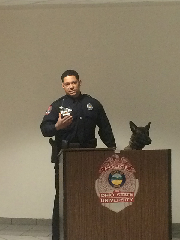 University Police Officer Bryan Thompson speaks at the ceremony with K-9 Ena by his side. Credit: Aubrey Cornwell | Lantern Reporter