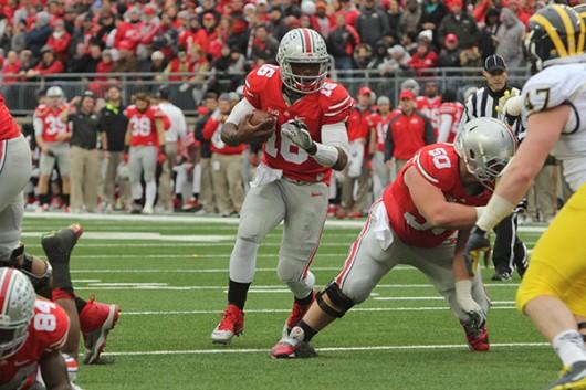 Then-redshirt freshman quarterback J.T. Barrett (16) runs with the ball during a game against Michigan on Nov. 29 at Ohio Stadium. OSU won, 42-28. Credit: Lantern File Photo