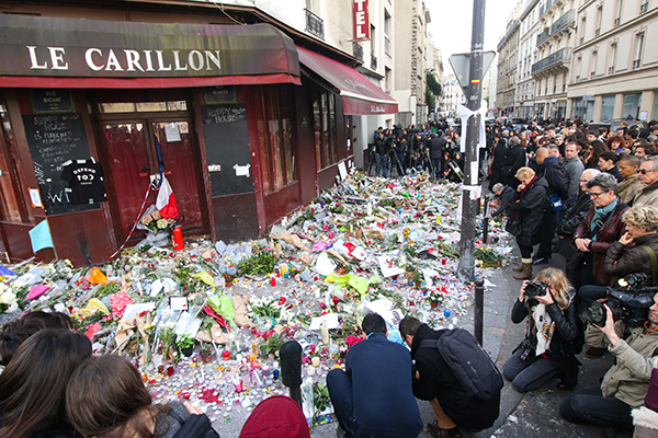 People lay flowers and candles in front of the Le Carillon restaurant, one of the first locations hit by Friday's attacks, together with the Petit Cambodge restaurant, in Paris on Nov. 16. Credit: Yann Schreiber | For The Lantern
