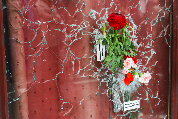 Flowers have been placed in a bullet hole at Le Carillion restaurant, seen Nov. 16. Credit: Yann Schreiber | For The Lantern