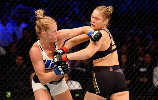 Holly Holm (L) throws a left-handed punch against Ronda Rousey (R) in the first round of their UFC women's bantamweight championship bout during the UFC 193 event at Etihad Stadium on Nov.15 in Melbourne, Australia. Credit: Photo by Josh Hedges/Zuffa LLC/Zuffa LLC via Getty Images