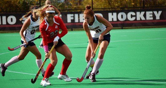OSU junior forward/midfield Maddy Humphrey (23) protects the ball from California sophomore midfield/back Mara Gutierrez (24) and redshirt junior back Michaela Swensen (18) during a field hockey game on Oct. 25, 2015, at Buckeye Varsity Field. Credit: Lantern File Photo