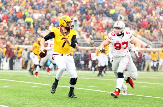 OSU then sophomore defensive lineman Joey Bosa (97) runs after Minnesota then redshirt-sophomore quarterback Mitch Leidner (7) during a Nov. 15 game in Minneapolis. OSU won, 31-24.