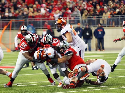 OSU players attempt to take down Illinois then junior running back Josh Ferguson (6) during a game on Nov. 1, 2015 at Ohio Stadium. Credit: Lantern File Photo