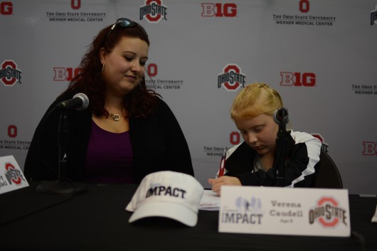 Verena (right) signs her official letter, signifying her spot on the OSU synchronized swimming team through Team IMPACT, while her mother, Ashley, looks on. Credit: Kevin Stankiewicz | Assistant Sports Editor