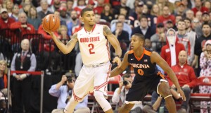 OSU junior forward Marc Loving (2) looks to pass the ball to a teammate while being defended by Virginia's Devon Hall (0) during a game on Dec. 1 at the Schottenstein Center. Credit: Bree Wililams | Lantern photographer