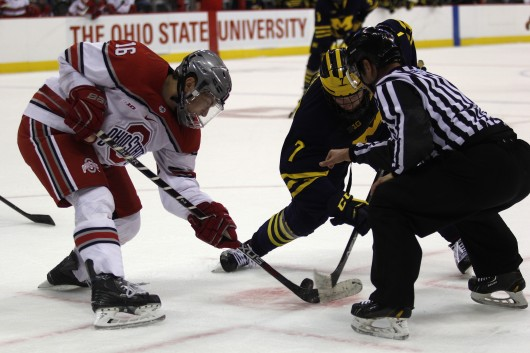 OSU sophomore forward Matthew Weis (16) tries to corral the puck during a face-off in a game against Michigan on Jan. 15. OSU won in a shootout. Credit: Kevin Stankiewicz | Asst. Sports Editor