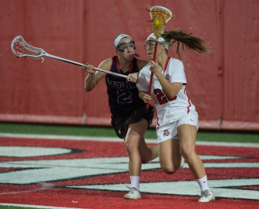 Sophomore midfielder Emily Mongno (28) runs with the ball during a game against Detroit on Feb. 13 at the Woody Hayes Athletic Center. OSU won 22-8. Credit: Courtesy of OSU