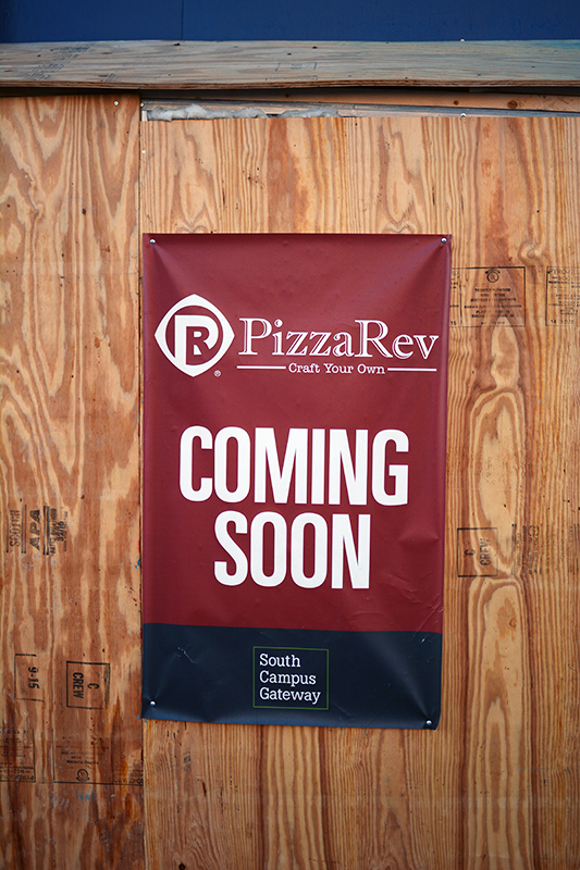 A sign hangs promoting the soon to be PizzaRev on high street. Credit: Kevin Stankiewicz | Asst. Sports Editor