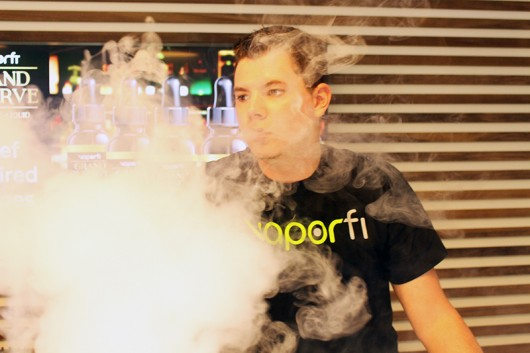 Cody Byrd, a third-year in business and marketing, vapes at Vaporfi, 2471 N. High St, his place of employment. Credit: Hannah Herner   Assistant Arts&Life Editor