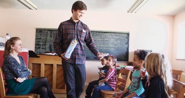 Zach Whittington passes out snacks to children before starting a lesson at the children's choir program at Summit on 16th United Methodist Church.  Credit: Kyjah Coryat | Senior Lantern reporter