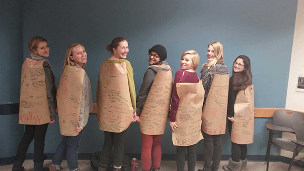 Members of the Girls Circle Project donned capes with motivational quotes written on them as part of a Women's Circle curriculum activity. Credit: Courtesy of Molly Duerre