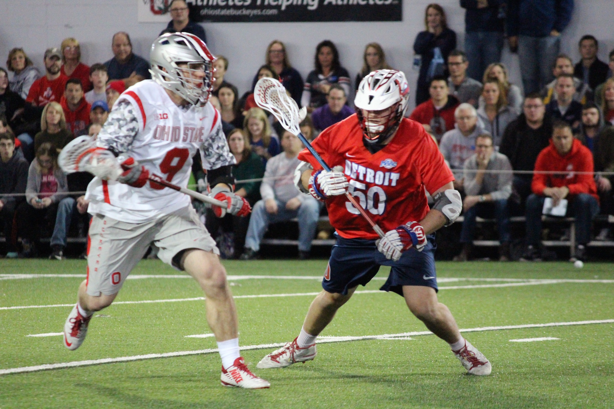 OSU junior attackman JT Blubaugh (9) moves past Detroit senior midfielder Mike Spuller (50) during the Buckeyes' contest with the Titans at the Woody Hayes Athletic Center on Feb. 13. OSU won 16-5. Credit: Miles McQuinn | Lantern photographer
