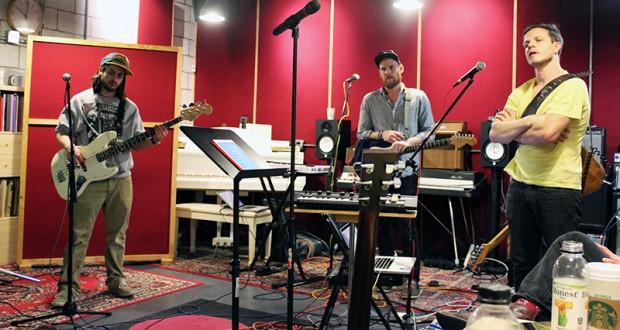 Bassist Seth Bain, guitarist and keyboardist Joseph Barker and guitarist Kerry Henderson focus on directions for the setup of an upcoming performance. Credit: Zak Kolesar | Lantern reporter
