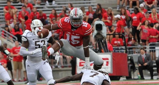 Then-OSU running back Ezekiel Elliott (15) leaps over a defender during a game against Western Michigan on Sept. 26 at Ohio Stadium. Credit: Samantha Hollingshead | Photo Editor