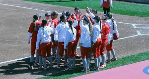 Members of the OSU softball team huddle outside the dugout during a game against Maryland. Credit: Lantern File Photo