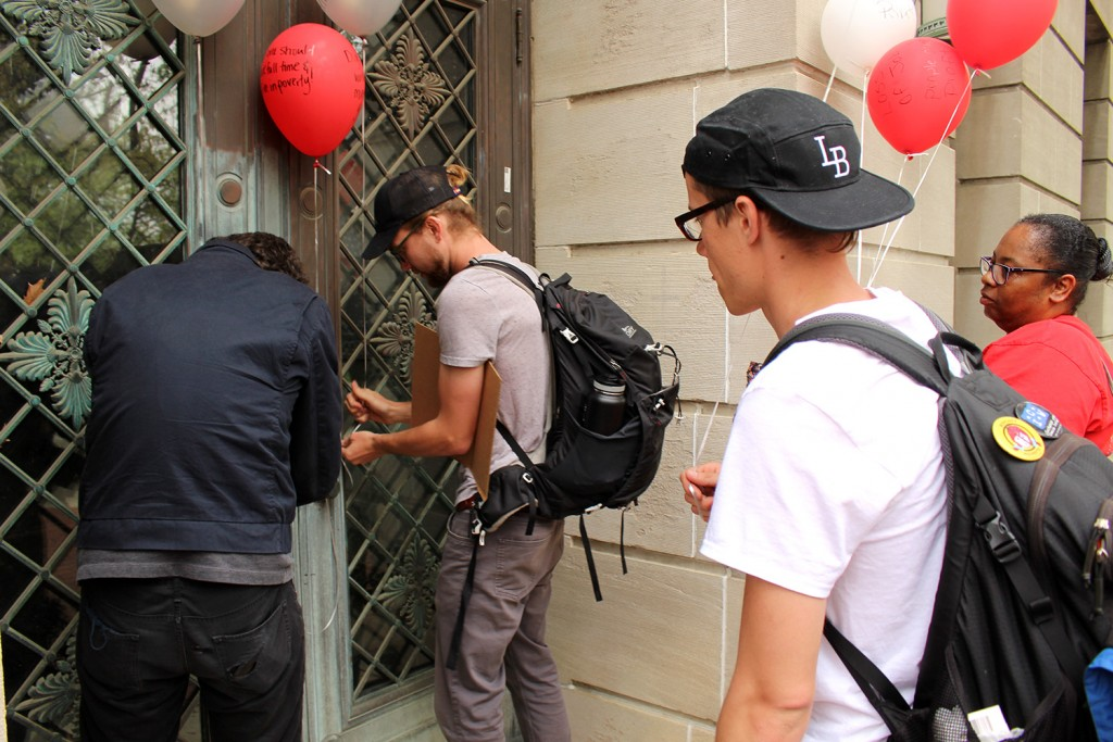 Protesters tie the balloons to the doors of Bricker Hall as a peaceful way to send a message to university administration. Credit: Hannah Herner | Assistant Arts&Life Editor