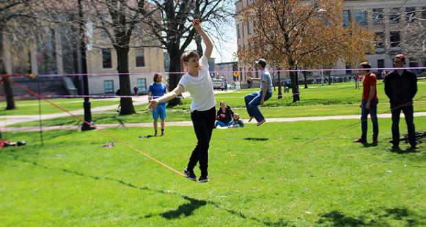 Alex Mason walks along a slackline on the Oval on April 12. Credit: Hannah Herner | Assistant Arts&Life Editor