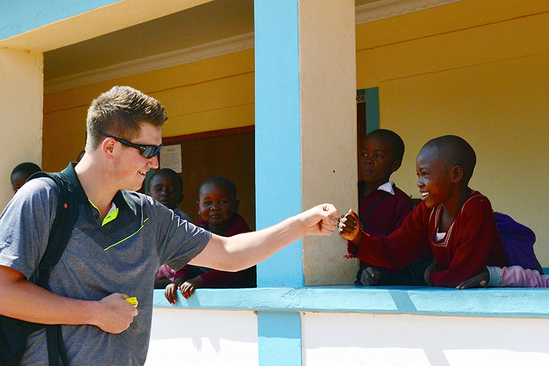 Tyler Pica, a 2015 Ohio State graduate in civil engineering, fist-bumps with a Tanzanian child during an August 2015 visit to several rural Tanzanian villages as part of an engineering capstone trip co-sponsored by the Global Water Institute. Credit: Courtesy of Michael Hagenberger