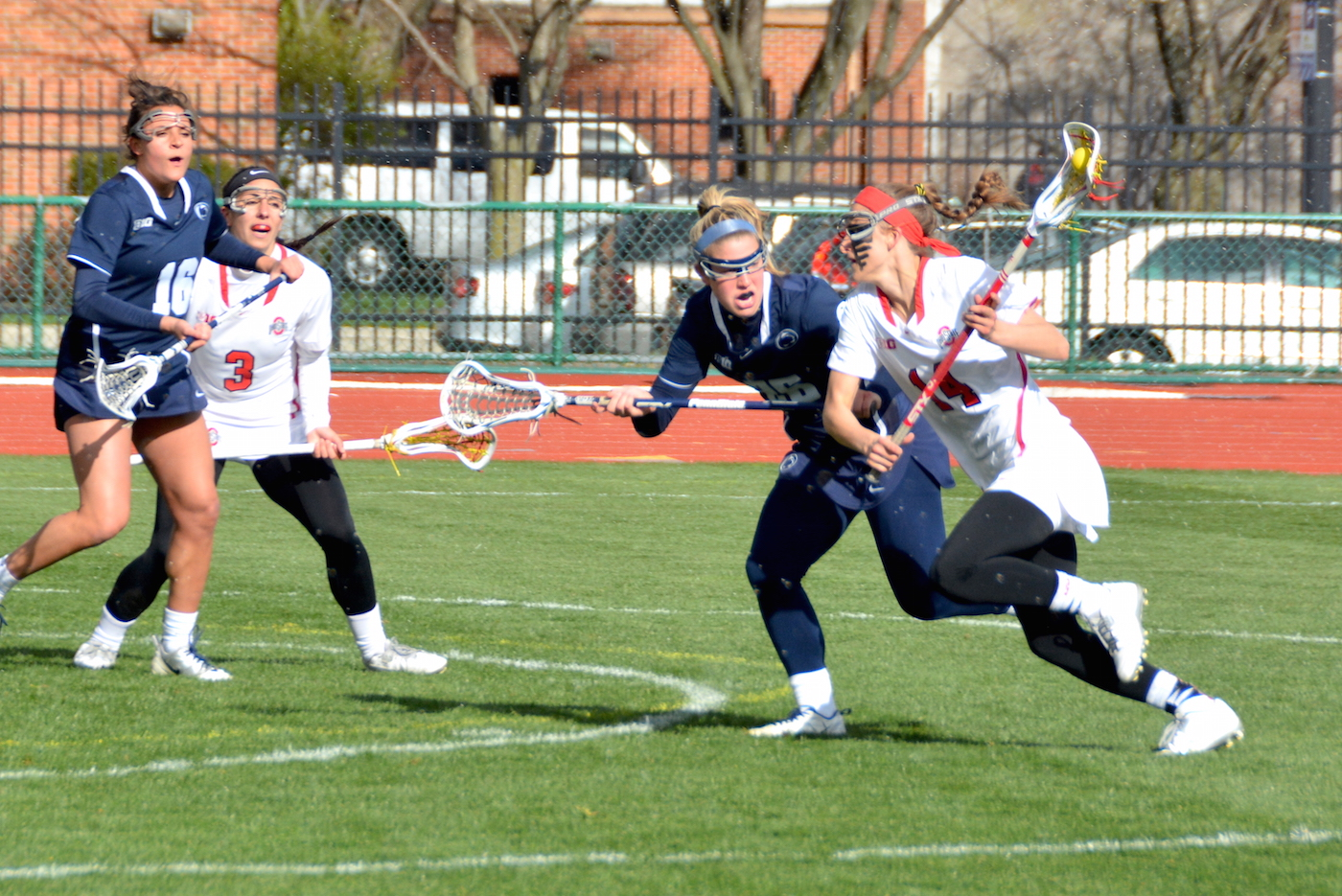 OSU senior attackman Cian Dabrowski (14) charges forward with the ball while Penn State senior Ally Heavens (26) plays defense during a game in Columbus on April 9. Credit: Evan Szymkowicz   Sports Director