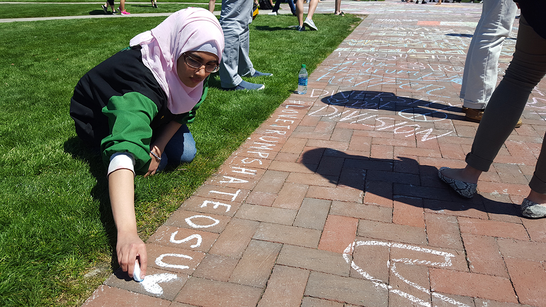 Fatimah Masood, a second-year in biochemistry, chalks a message on the Oval on April 15. Credit: Michael Huson | Campus Editor