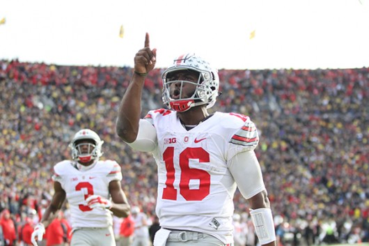 OSU then redshirt-sophomore quarterback J.T. Barrett (16) celebrates after a touchdown during a game against Michigan on Nov. 28 at Michigan Stadium in Ann Arbor, Michigan. Credit: Lantern file photo