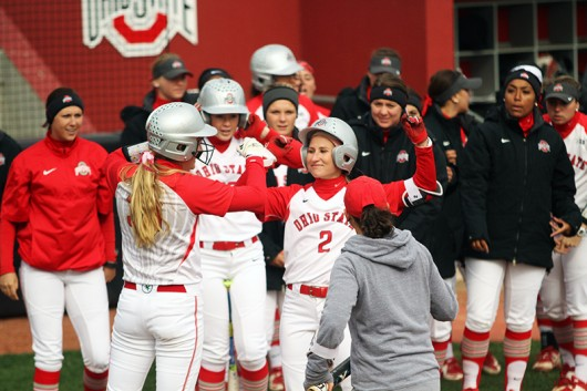 OSU junior Alex Bayne (2) is welcomed by her teammates at home plate after hitting a homerun during a game against Penn State on April 6 at Buckeye Field. Credit: Samantha Hollingshead | Photo Editor