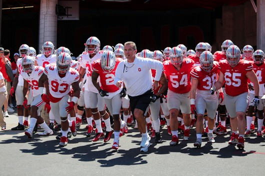 OSU coach Urban Meyer and members of the OSU football team run into the field before the spring game on April 16 at Ohio Stadium. Credit: Lantern file photo