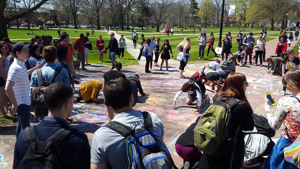 Ohio State students gather to chalk over a message that supports Republican presidential candidate Donald Trump on Friday on the Oval. Credit: Michael Huson | Campus Editor