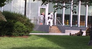 A man enters the Chemical and Biomolecular Engineering and Chemistry building in a white suit.