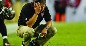 Then-Tampa Bay Buccaneers head coach Greg Schiano crouches on the field during a time out on Sept.15, 2013, in Tampa, Florida | Courtesy of TNS