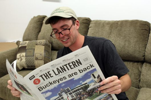 Nick Roll reads a newspaper while sporting dad-style fashions. Credit: Alexa Mavrogianis | Photo Editor