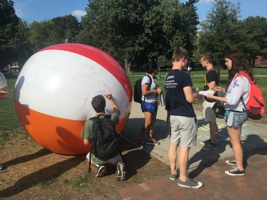 Students sign a large, inflatable beach ball on The Oval in an effort to promote free speech on campus on Sept. 14. Credit: Summer Cartwright | Lantern Reporter