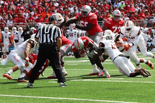 OSU junior H-back Curtis Samuel (4) attempts to break a tackle during the first half of the Buckeyes' season opener against Bowling Green on Sept. 3 at Ohio Stadium. The Buckeyes won 77-10. Credit: Alexa Mavrogianis | Photo Editor