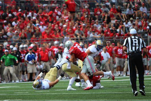 OSU redshirt sophomore defensive end Sam Hubbard (6) sacks Tulsa redshirt senior quarterback Dane Evans during the first quarter against Tulsa on Sept. 10. The Buckeyes won 48-3. Credit: Alexa Mavrogianis | Photo Editor