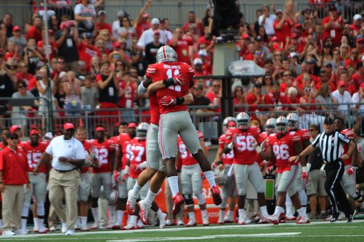 OSU redshirt sophomore defensive end Sam Hubbard and OSU junior defensive end Jayln Holmes (11) celebrate after Hubbard's sack during the first quarter against Tulsa on Sept.10. The Buckeyes won 48-3. Credit: Alexa Mavrogianis | Photo Editor