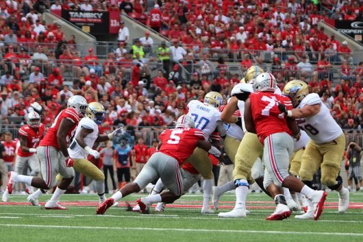 OSU junior linebacker Raekwon McMillan (5) tackles Tulsa redshirt senior running back James Flanders (20) from behind during the first quarter against Tulsa on Sept.10. The Buckeyes won 48-3. Credit: Alexa Mavrogianis | Photo Editor