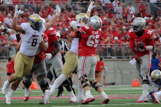 OSU redshirt senior offensive linesman Pat Elflein (65) blocks a pass rusher from OSU redshirt junior quarterback J.T. Barrett (16) during the fourth quarter of the Buckeye's game against Tulsa on Sept. 10. The Buckeyes won 48-3. Credit: Alexa Mavrogianis | Photo Editor